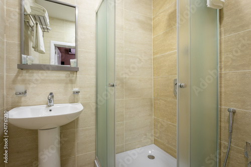 Bathroom Tiles And Bright Colors Of Broom Shower With Frosted Doors Mirror Above The Sink Hanging A Towel Over The Toilet On A Hanger Buy This Stock Photo And Explore Similar Images At