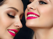 Closeup Portrait Of Two Young Beautiful Smiling Women. Bright Pink Lipstick. Skin Care, Cosmetics, SPA Therapy Or Cosmetology Concept