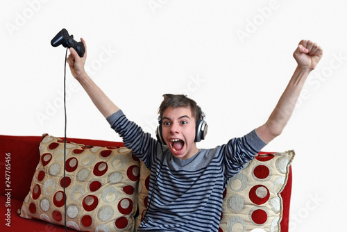 Photo teenage boy with headphones on his head emotionally with cries of plays in a gam