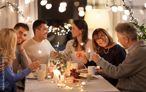 Fototapety, obrazy: celebration, holidays and christmas concept - happy family with sparklers having fun at dinner party at home