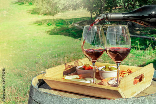 Wine tasting. Two glasses of red wine with snacks on a barrel outside a winery, with blurred greenery in the background as a place for text - 247770088