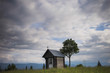 Old weathered small wooden chapel isolated in beautiful countryside landscape. Horizontal color photography.