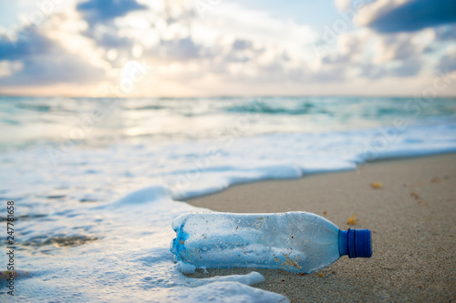 Fotografia, Obraz  Used plastic water bottle washed up on the shore of a tropical beach, highlighti