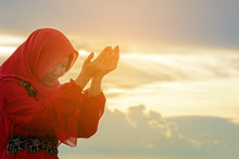 Veiled Islamic Muslim Woman Wearing A Burka Standing And Praying In The Sunset