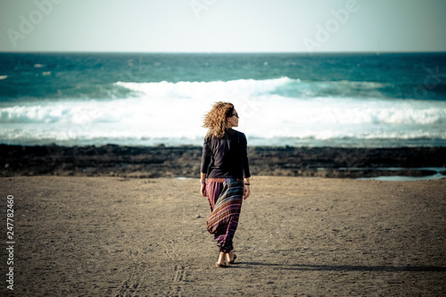 Fotografia One woman walking at the beach to the ocean and waves enjoying the feeling of fr