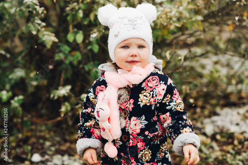 Photo  Little attractive girl playing and walking at garden in snow weather
