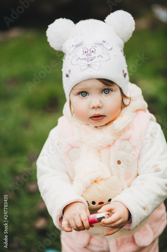 Portrait of cute and pretty little girl playing with toy and interesting looking at camera Canvas Print