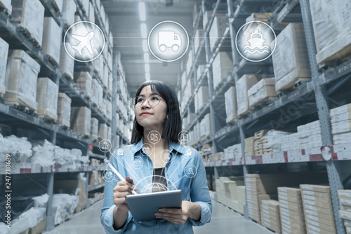 Fotografie, Obraz  Portrait of young attractive asian entrepreneur woman looking at inventory in warehouse with smart tablet in management technology,  international connected industry, asian small business sme concept