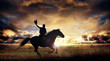 A silhouette of a cowboy and horse at sunset