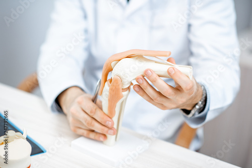 Obraz Close-up of the therapist showing knee joint model during the medical consultation - fototapety do salonu