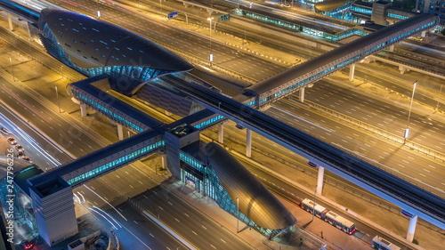 Fototapeta Futurystyczny budynek stacji metra i tramwaju w Dubaju i luksusowe drapacze chmur za timelapse nocy
