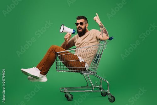 Leinwand Poster bearded man with megaphone pointing up while sitting in shopping cart isolated o