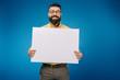Leinwandbild Motiv cheerful man holding blank placard isolated on blue