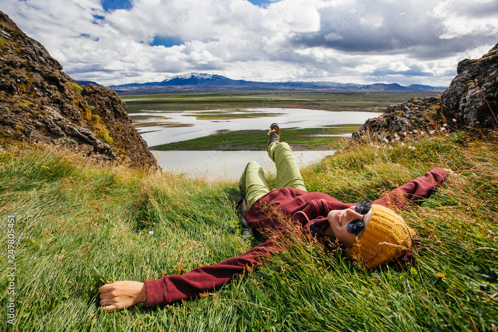 Fototapeta Happy young woman in bright clothes traveling Iceland, enjouing nature