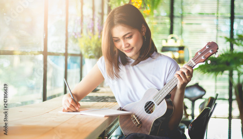 Fotomural Female composer is writing music in a joyful feeling using ukulele as a device in the Vintage-style Café, Soft tone vintage style