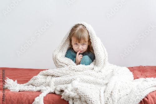 Fotografia, Obraz  The capricious little girl sits on a bed at home.