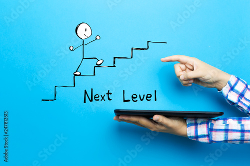 Fotomural Next level concept with a tablet computer on a blue background