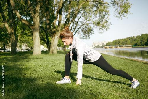 Summer portait of athletic female wearing leggings, hoodie