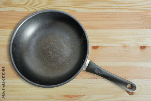 Fotografie, Obraz  Scratches on the old teflon frying pan on wooden floor, top view