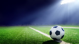 Fototapeta sport - Tradition soccer ball illuminated by stadium lights