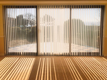 Sunlight Shining Through Full Length White Vertical Blinds In Front Of Three Glass Sliding French Doors Leading To A Patio, Garden And Sea View, Creating Shadow Stripes.