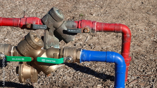 Photo  Red and blue water lines with backflow preventer