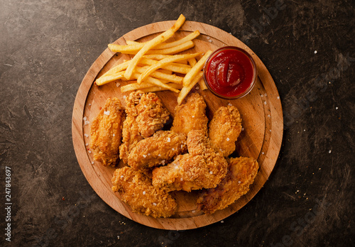 Fototapeta Fried in breaded chicken wings and french fries obraz