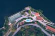 Eine Stadt am Wasser mit Sportplatz aus der Luft