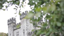 A Close Up On A Castle Turret Pulls Focus To The Windy Green Tree Leafs And Branches In The Foreground