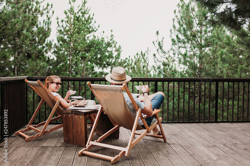 Fototapeta Young couple enjoying coffee on the balcony in the mountains