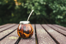 Yerba Mate Tea In Traditional Wooden Color Pumpkin Calabash With Metal Bombilla Straw In It, Outdoors On Garden Table. A Lot Of Copy Space.