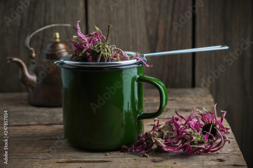 Fototapeta Enameled cup of healthy echinacea tea with tea infuser, dry coneflower herbs and vintage teapot on wooden table