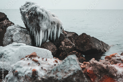 Fotografie, Obraz  Stones on the sea covered with ice and with hanging icicles from them