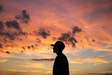 Side View Of Man Standing Against Cloudy Sky During Sunset