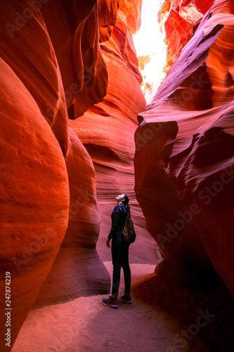 Fotografia Impressed young traveler woman looking up inside of the Antelope Canyon, Arizona, USA