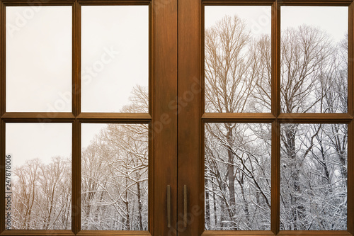 Old wooden window frame with winter view from outside.