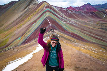 Young woman celebrating with the fist held high, after a long trekking through Vinicunca (rainbow mountain) Perú.