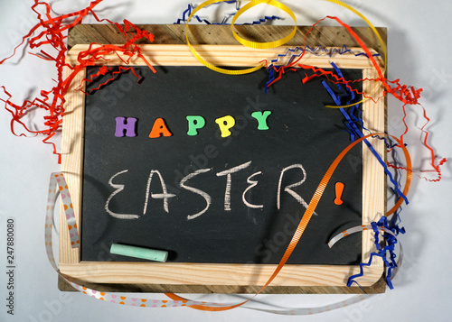 Valokuva  Happy Easter message on chalkboard with colorful ribbon and letters