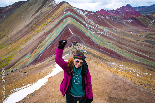 Foto  Young woman celebrating with the fist held high, after a long trekking through Vinicunca (rainbow mountain) Perú