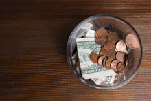 Donation Jar With Money On Wooden Background, Top View. Space For Text