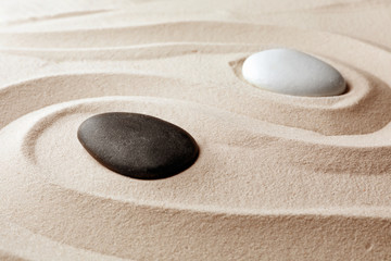 Fototapeta na wymiar Zen garden stones on sand with pattern. Meditation and harmony