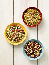 Three Different Bean Salads On A Rustic White Background