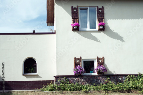 Fotografía two windows with flower pots on the facade of the building
