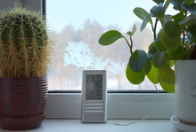 Home Electronic Thermometer Shows The Temperature Outside -37 Degrees Cold. Frost Froze On The Glass. Severe Cold Snap. Potted Flowers On A Plastic Window Sill