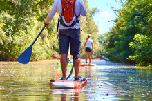 Close-up Of A Woman And Man Legs On Stand Up Paddle In Water