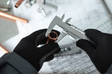 Engineer Is Holding In Hands A Brass Pipe And Is Measuring A Diameter By A Calipers. Pipework.