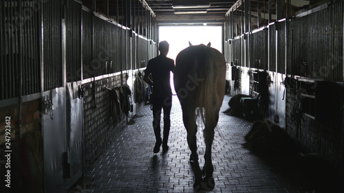 Fotografía  Young jockey walking with a horse out of a stable