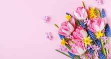 Beautiful Spring Flowers On Pastel Pink Table Top View. Greeting Card Or Banner For International Women Day. Flat Lay.