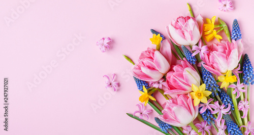 Poster Fleuriste Beautiful spring flowers on pastel pink table top view. Greeting card or banner for International Women Day. Flat lay.