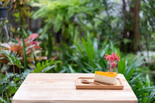Passion Fruit Cheesecake Serve On Wood Tay And Wooden Table With Dried Flower Vase Green Nature Background